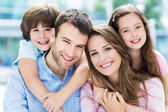 Happy young family hugging — Stock Photo