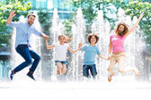 Happy young family jumping — Stock Photo