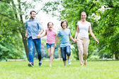 Happy young family running — Stock Photo