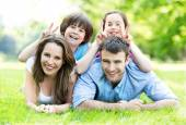Happy young family lying on grass — Stock Photo