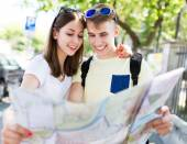 Smiling young couple with map — Stock Photo