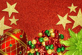 Christmas tree ornaments on red glitter background — Stockfoto