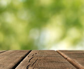 Wooden table top in a blurred country landscape — Stock Photo