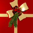 Golden bow with sprig of fir tree on red background — Stock Photo #52824095