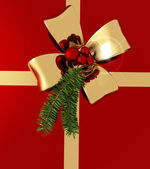 Golden bow with sprig of fir tree on red background — Stock Photo