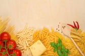 Varieties of pasta, cheese and tomatoes on wooden board — Stock Photo