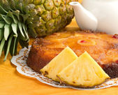 Upside down cake and fresh pineapple on orange tablecloth — Stock Photo