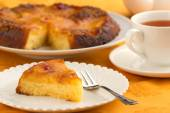 Pineapple cake and cup of tea on orange tablecloth — Stock Photo