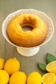 Ring-shaped cake and lemons on wooden table — Stock Photo