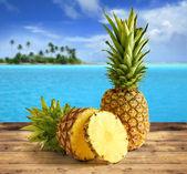 Pineapple on wooden table in a tropical landscape — Stock Photo