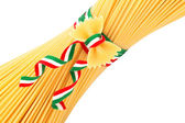 Bunch of spaghetti and farfalle tied by a tricolour strip — Stock Photo