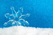 Ice crystal on snow in blue background — Stock Photo