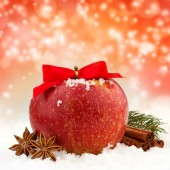 Apple with red ribbon and spices in the snow — 图库照片