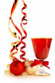 Red goblet, christmas baubles and satin ribbons on white background — Stock fotografie