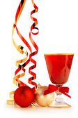 Red goblet, christmas baubles and satin ribbons on white background — Foto de Stock