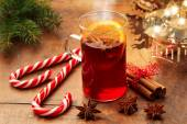 Mulled wine and candy canes by candlelight on wooden table — Stock Photo