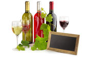 Wine bottles and glasses, blackboard and grapevine — Stock Photo