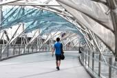 Young man walking inside the helix bridge — Stock Photo