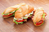 Three sandwiches with savoury fillings on wooden table — Stock Photo