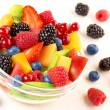 Close up of bowl with fruit cocktail and mixed berries scattered — Stock Photo #76220349