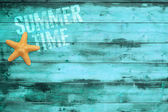 Sea star and summertime word printed on turquoise wooden plank — Stock Photo