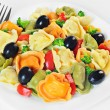 Salad made with tortellini, olives, broccoli, red pepper, on a plate — Stock Photo #79633830