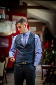 The serious young man in a vest and with hours — Stock Photo