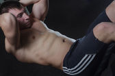 Young man trains the abdominal muscles of the abdomen — Stock Photo