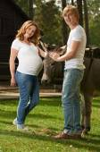 Pregnant couple with cute donkey — Stock Photo