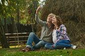 Couple taking self portrait near haystack — Stock Photo