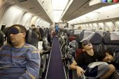 The passengers are sleeping in the cabin in flight. — Stock Photo