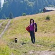 Woman hiking in mountains with dog — Stock Photo #54844169