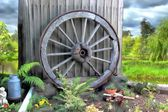 Garden display of an old historic wooden wagon wheel — Stock Photo
