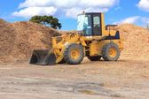Front end loader with piles of chip bark — Stock Photo