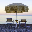 Two empty chairs stand on beach under open umbrella overlooking — Stock Photo #61765305