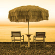 Two empty chairs stand on beach under open umbrella overlooking the marine sunrise — Stock Photo #61765319