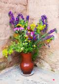 Bouquet of wild flowers in a clay jug — Стоковое фото