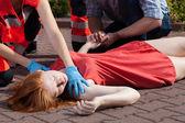 Paramedic helping unconscious woman — Stock Photo