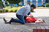 Man trying to help unconscious woman — Stock Photo