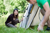 Woman and man pitching a tent — Stockfoto