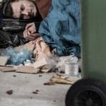 Homeless man lies with trash — Stock Photo #52499689