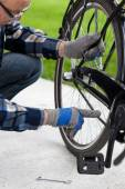 The man checks the chain from the bicycle — Stock Photo