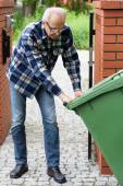 Man is pulling wheeled dumpster — Stock Photo