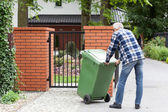 Man is pushing wheeled dumpster — Stock Photo