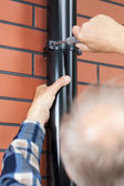 Man with a screwdriver screwed gutter — Stock Photo