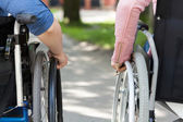 Couple of friends on a wheelchair — Stockfoto