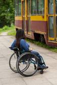 Disabled girl waiting for a tram — Stockfoto