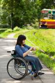 Girl on wheelchair waiting for tram — Stock Photo