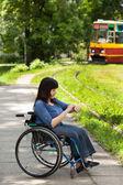 Girl on wheelchair waiting for tram — Stockfoto