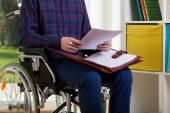 Man on wheelchair reading documents — Стоковое фото